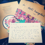 A photograph of three print copies of issue one of Doll Hospital Journal with a handwritten postcard placed on the top