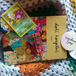 A photograph of Doll Hospital Issue One, a lollipop, two doll hospital stickers and a Pokemon card of Koffing on a colourful crochet blanket